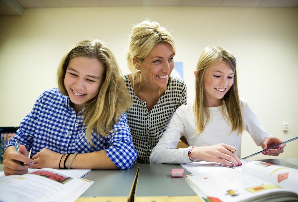 Lärare som hjälper två elever. Foto: Sören Håkanlind