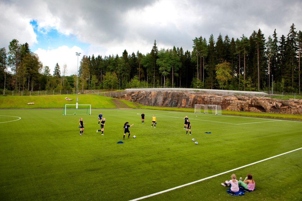 Bild på ungdomar som tränar på en fotbollsplan.