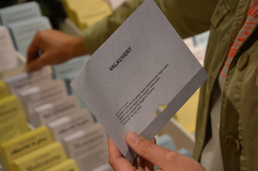 Bild på en hadn som håller ett valkuvert vid röstsedelstället.