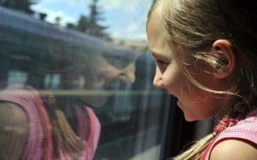 Bild på en flicka som tittar ut ur ett tågfönster.