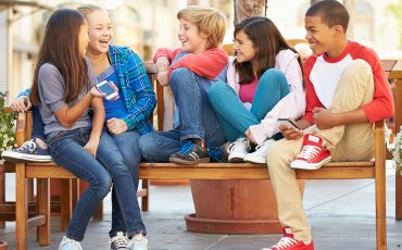Ungdomar som sitter på en bänk
