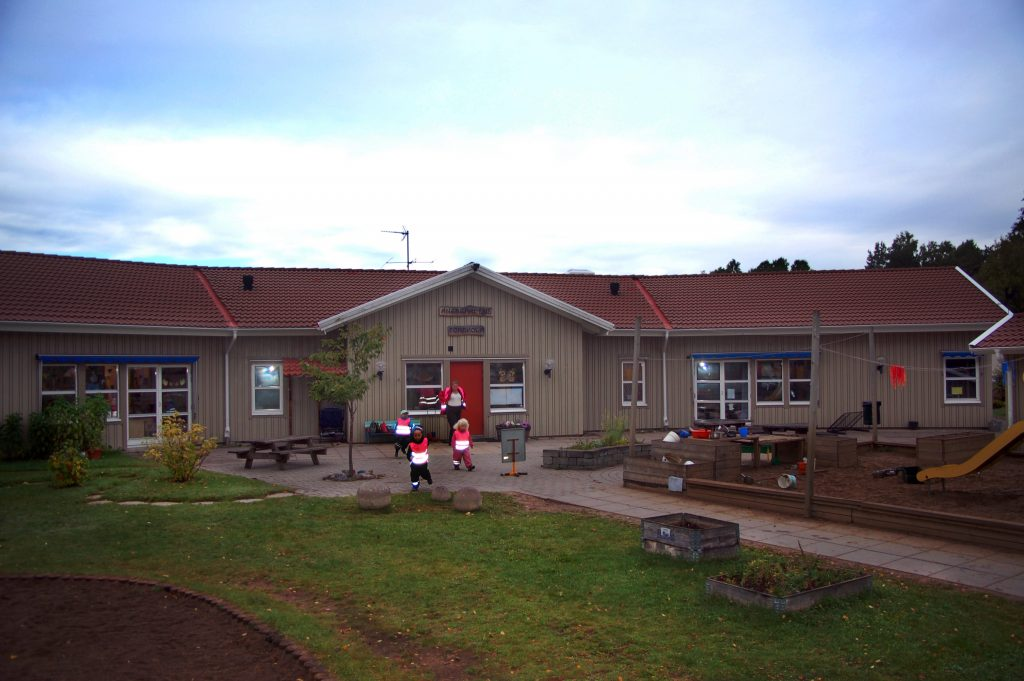Bild på Ängsgårdens förskola som är ett grått enplanshus med röd entrédörr.