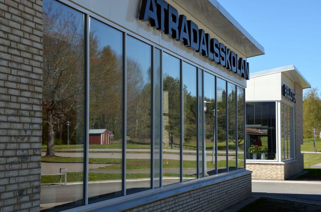 Bild på glasparti på Ätradalsskolan. på bilden ses också en fasadskylt med skolans namn.