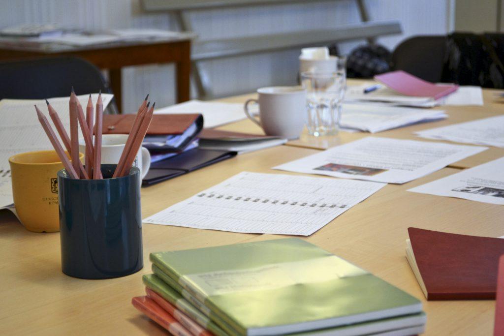 Bild på ett arbetsbord med papper, böcker och pennor på.