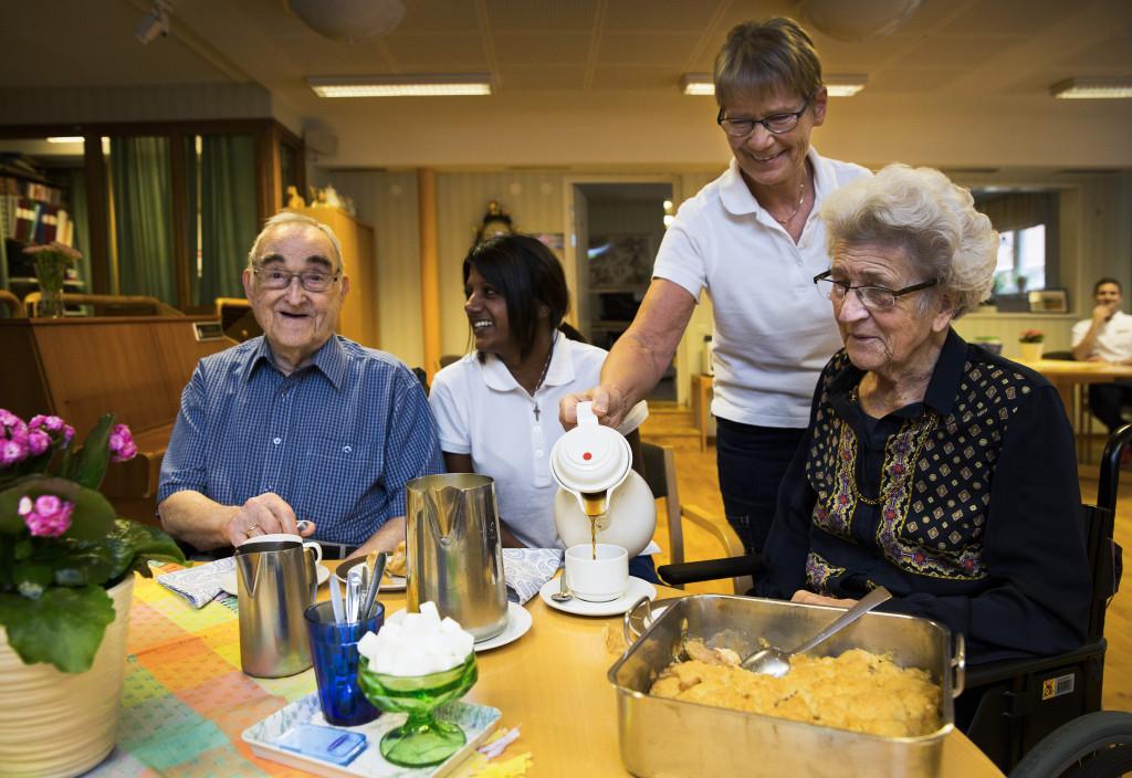 Äldre och personal fikar. Foto: Sören Håkanlind