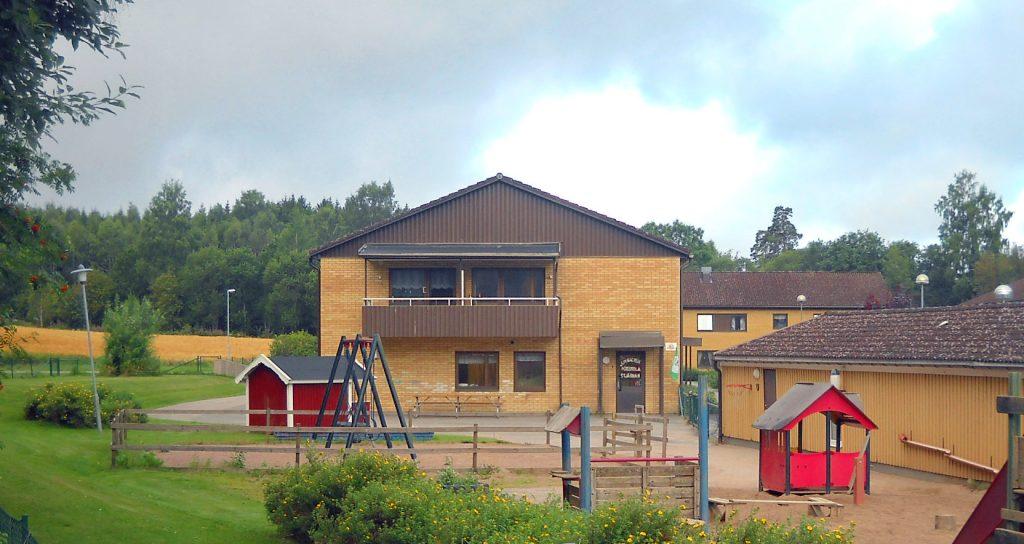 Bild på junibackens förskola med lekplatsen i förgrunden. huset är av gult tegel och brunt trä och är i två våningar