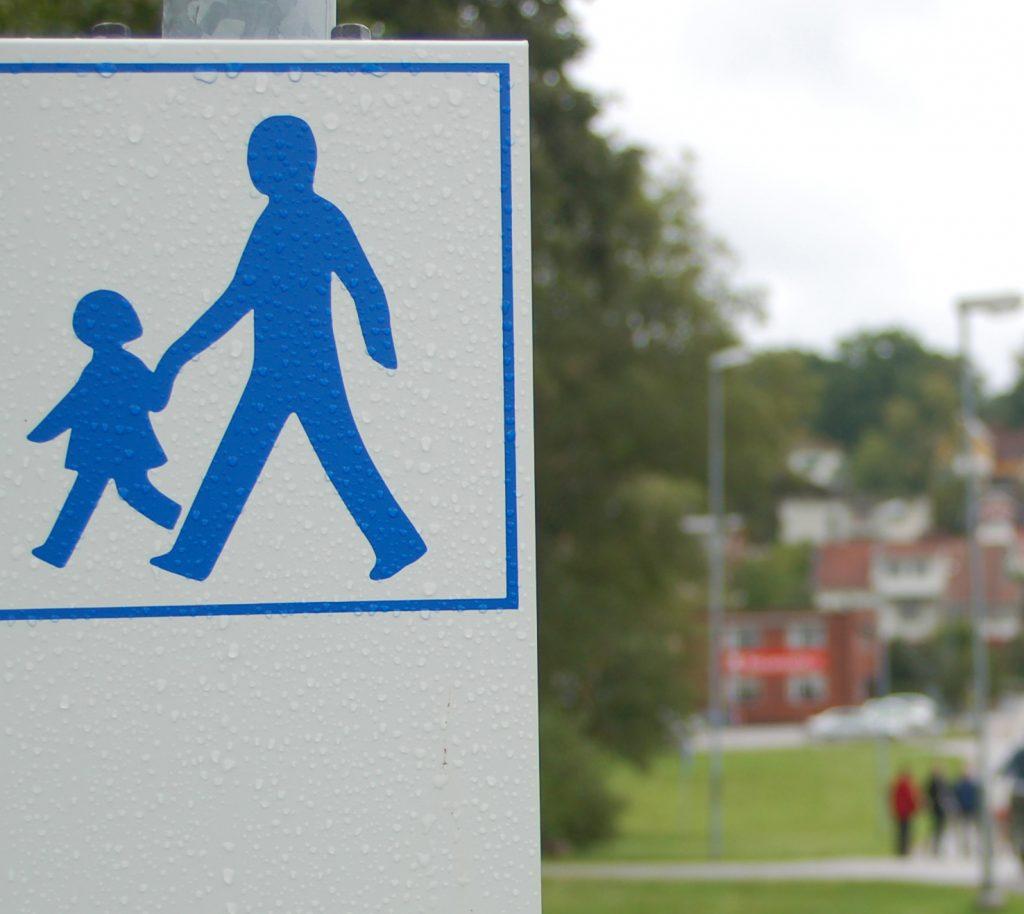 Bild på en vit skylt med två blå gubbar som symboliserar promenadstråk att följa.