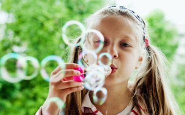 En flicka som blåser såpbubblor