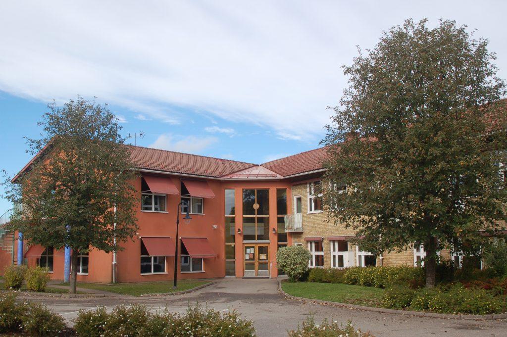 Bild på Hökerums skola som har två våningar och är byggd i terrakottafärgad och beige puts