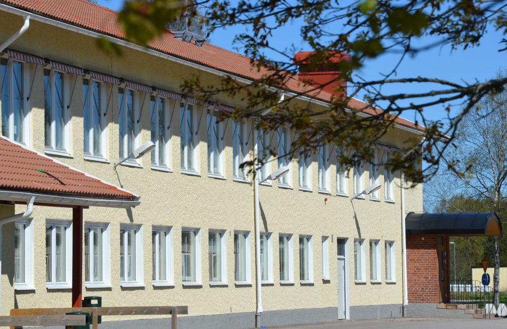 Bild på delar av Timmele skola som är en ljusgul stenbyggnad i två våningar