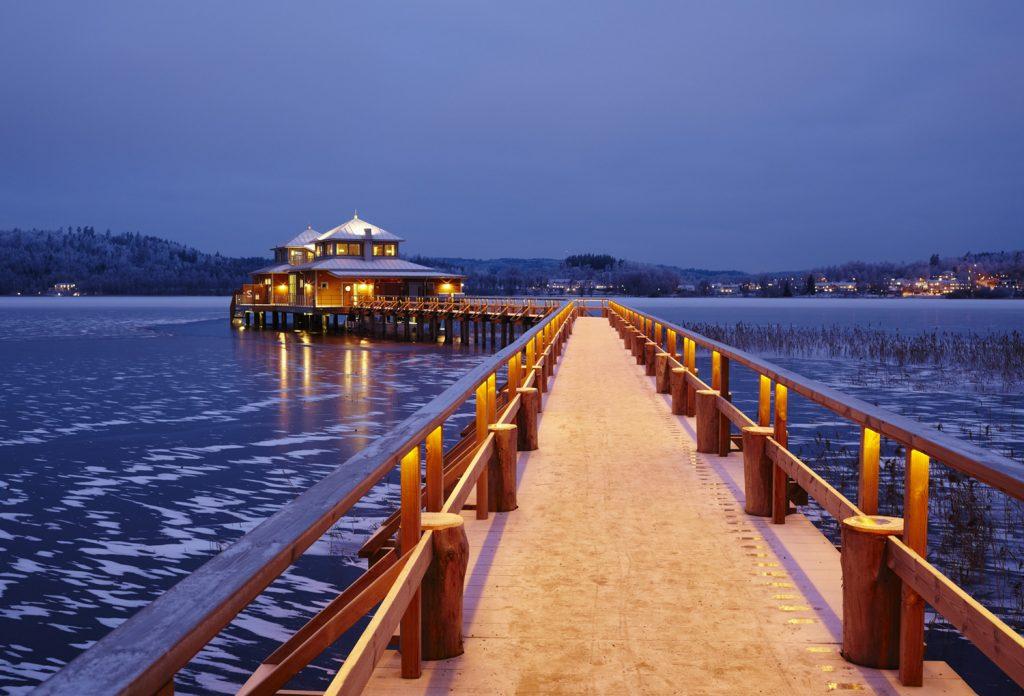 Bild på Kallbadhuset i Ulricehamn. Bilden är tagen kvällstid där lamporna lyser upp träbron ut till kallabdhuset som står på pålar i vattnet.