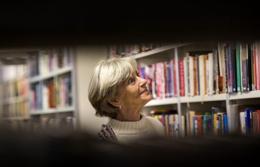 Kvinna bland böcker och bokhyllor på biblioteket.