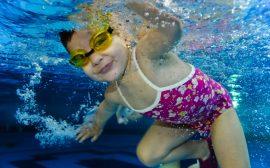 Barn som simmar under vattnet