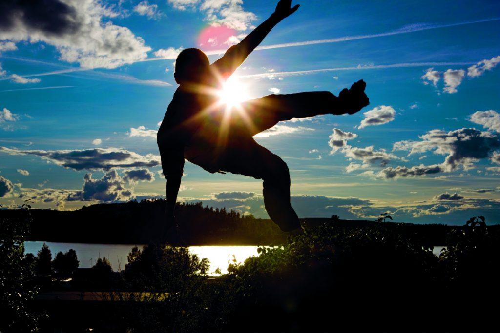 Bild på en kille som hoppar med himlen som bakgrund och solen i motljus.