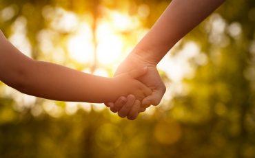 Bild på vuxen och barn som håller varandra i handen