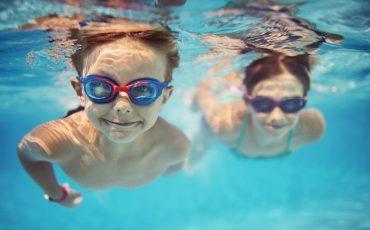 en flick och en pojke som simmar i en pool