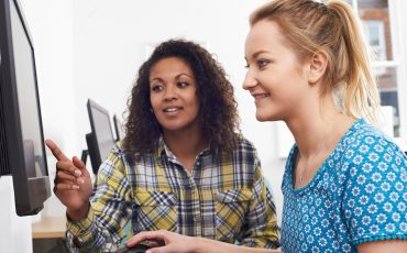 Två kvinnor som sitter vid en dator