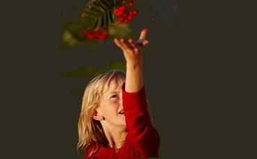 tjej som sträcker sig efter rönnbär. Foto: Jan Töve