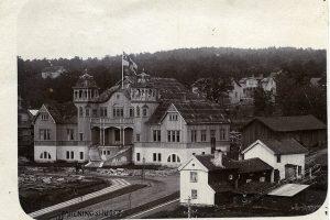 Svartvit foto på en pampig byggnad med tinnar och torn som är Folkets hus och som ligger i stadsmiljö.