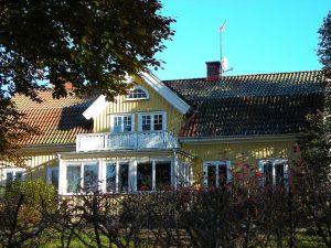 Bild på ett gult trähus med rött tegeltak och vita knutar. Huset har två våningar och en balkong.