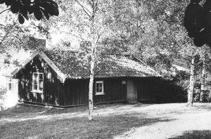 En svartvit bild på en liten låg stuga med tegeltak omringad av björkar.