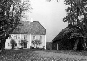 Svartvit bild på ett herrgårdsliknande hus i ljusfärg. Bredvid finns en mörkare träbyggnad.