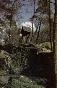 En bild på en Klockstapel och träd runt omkring.