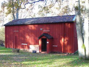 En röd gammal träbyggnad i rött. För fönstren sitter träluckor.