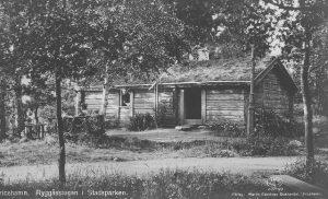 Svartvit bild av en gammal låg stuga byggd av liggande stockar.