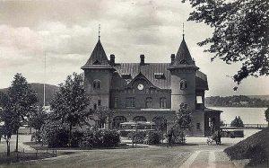 Svarvit bild på stationshuset I Ulricehamn. Tegelbyggnad med två torn.