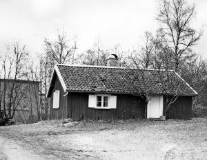 Svartvitt foto på en liten toparbyggnad med vita fönster och dörr.