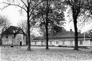 Svartvit bild på en äldre stenbyggnad och bredvid en säteribyggnad