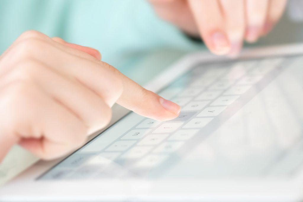 Händer som trycker på en skärm på en surfplatta