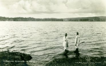 Svartvitt foto från 1920-talet med två kvinnor som stå i vattenbrynet av Åsunden