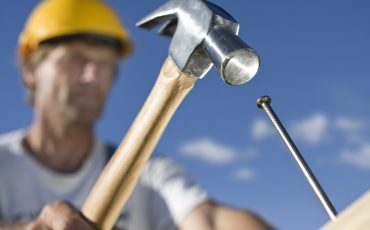 Person som slår i en spik med en hammare