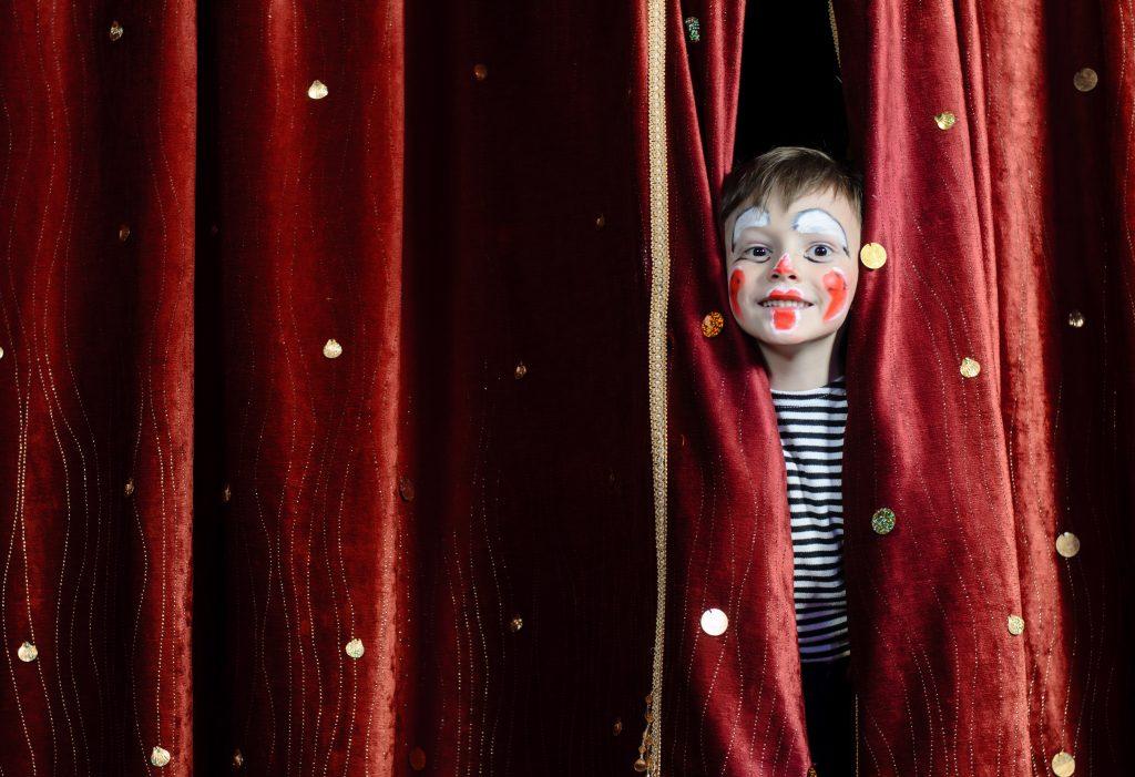 Pojke kikar fram genom en teaterridå