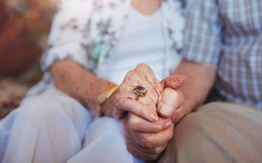 Äldre personer som håller varandra i handen