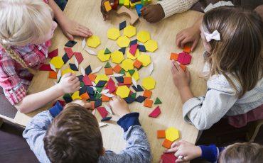 Barn som leker runt ett bord