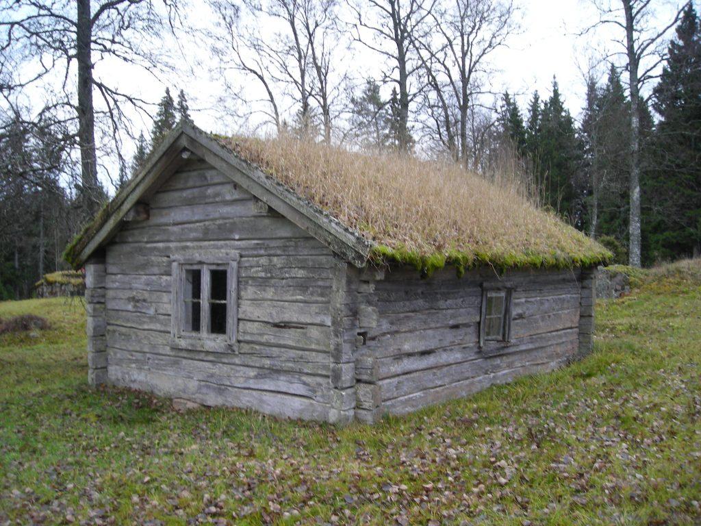 En liten torpstuga med gräs på taket placerad i en glänta