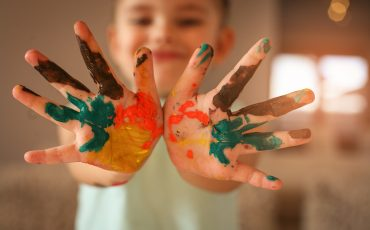 Barnhänder med färg på