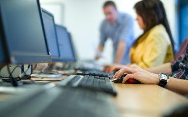 Personer spm sitter framför datorer