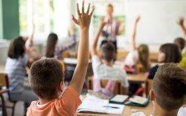 Barn som räcker upp handen i ett klassrum