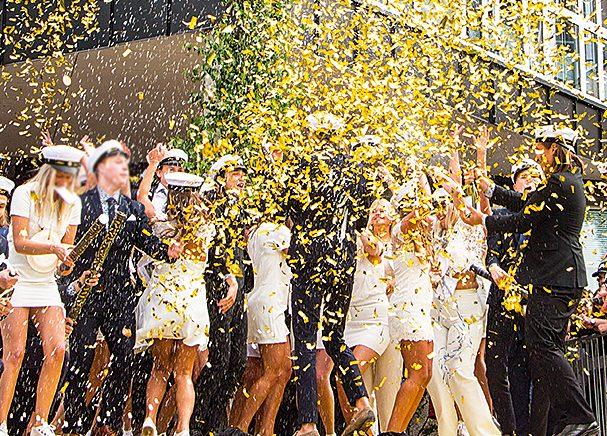 Bild på ungdomar som tar studenten i vita kläder och vita studentmössor. Det kastas konfetti och feststämning råder.