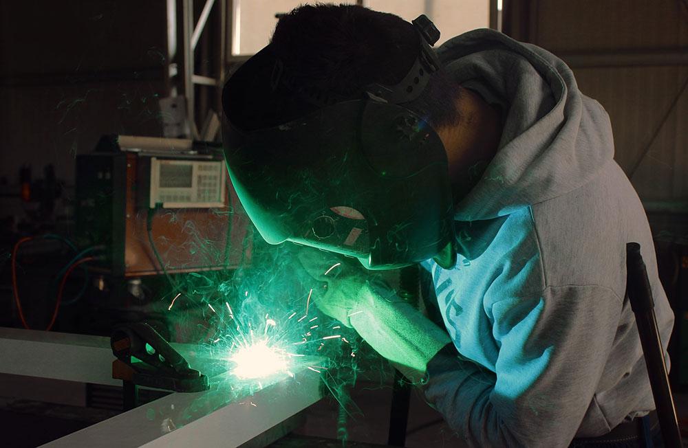 Bild på en elev som svetsar med en svetsmask på sig. Ett starkt sken kommer från svetslågan.