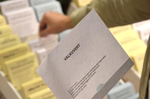 En person håller ett valkuvert i handen