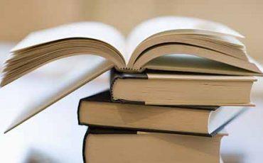En trave med böcker varav den översta ligger uppslagen.