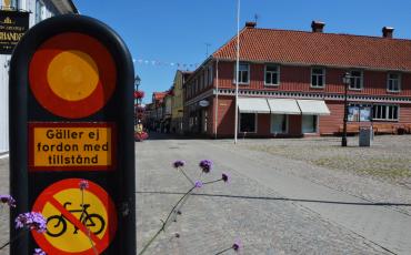Bild på en vägskylt med förbud för cykeltrafik och motorfordon. i bakgrunden stora torget och gågatan i Ulricehamn.