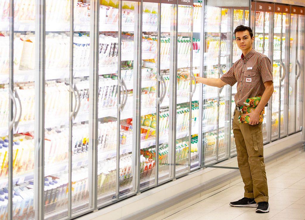 Bild på en elev som praktiserar i en livsmedelsbutik. Han står vid kyldisken