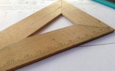 Vinkelhake i trä, papper och en penna