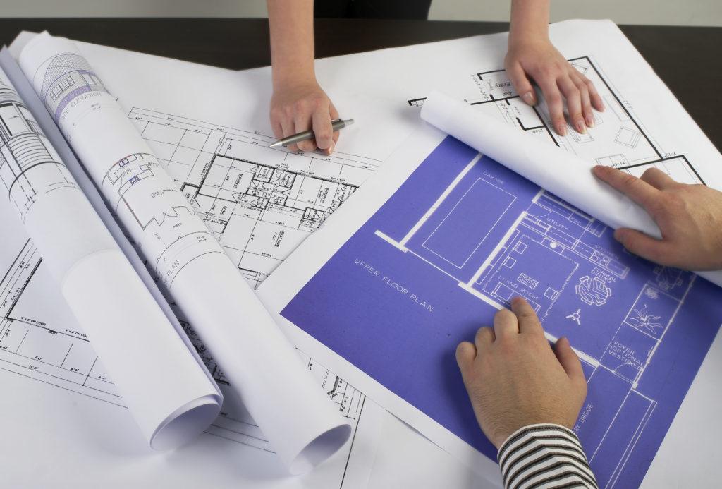 Bild på händer vis byggritningar på ett bord.